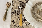 Vintage place setting with silver forks on lace tablecloth