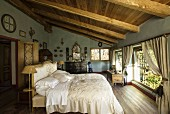 Antique furniture and elegant, vintage-style bed linen in country-style attic bedroom