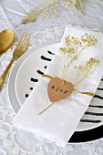 Heart-shaped tag and dried flower sprayed gold on napkin