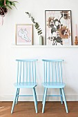 Two Windsor chairs painted pale blue below pictures on narrow shelf