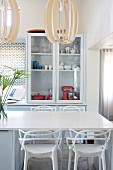 Dining table and modern chairs in pale blue and white kitchen