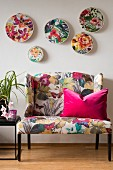 Floral fabrics in embroidery hoops mounted on wall above sofa with floral print upholstery