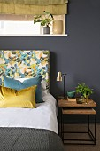 Bed with floral headboard and nest of bedside tables against dark wall