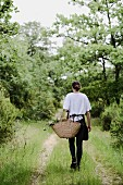 Woman carrying raffia shopping basket along track through woodland