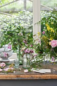 Vases of wildflowers on worn table below window