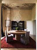 Old ceiling fresco above large round wooden table in dining room