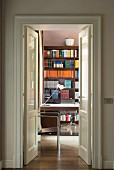 Bookcase in study seen through open double doors
