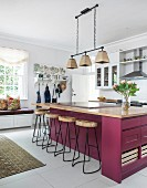 Berry-coloured island counter and delicate bar stools in bright kitchen