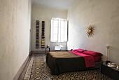 Simpel eingerichtetes Schlafzimmer mit gemustertem Boden