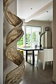 Wooden sculpture in front of black dining table and designer chair