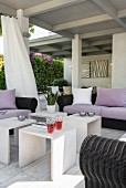 Comfortable black rattan sofas with mauve cushions and scatter cushions and several sire tables on roofed terrace