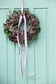 Autumnal wreath with pink lace ribbons on vintage wooden door