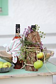 Autumnally decorated bottles wrapped in bark and heather with green apples tied with cord