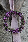 Romantic heather wreath hung from rustic wooden upright