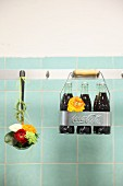 Flowers in ladle and bottle rack hanging from hooks