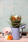 Arrangement of ranunculus and bilberry twigs in old enamel coffee pot