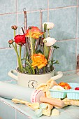 Ranunculus and whisks arranged in old saucepan