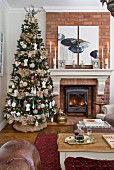 Decorated Christmas tree next to fireplace in living room