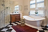 Free-standing bathtub and chequered floor in classic bathroom