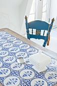White china pot on table with blue and white, patterned, tiled top and oak frame