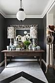 Üppig dekorierter Tisch im Eingangsbereich mit dunklen Wänden