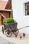 Metal hen ornaments in front of plants in old wooden cart