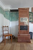 Old tiled stove against wall with partially uncovered historical mural