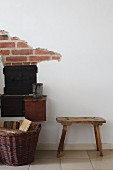 Old wooden footstool next to fireplace with exposed brickwork above