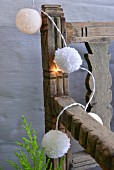 Hand-made fairy lights with white baubles and wool pompoms