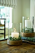 Pillar candles in glass and wood lanterns decorated with sprigs of rosemary