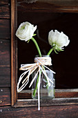 Ranunculus in glass bottle decorated with plaited raffia