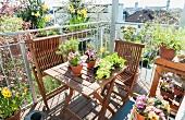 Balkon mit Holzmöbeln und Frühlingsblumen