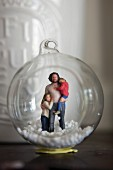Figurines and artificial snow in glass bauble