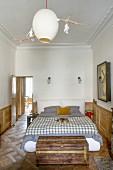 Schlafzimmer in einem Altbau mit Kassettenverkleidung und Parkett