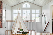 Children's teepee on landing with bank of windows in background
