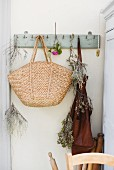 Raffia shopping bag, dried herbs and apron hanging from coat pegs