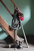 Nostalgischer Rucksack mit Wanderstock und Bündel mit roten Hagebutten an Vintage Holzstiege