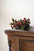 Posy of rose hips on top of vintage chest of drawers