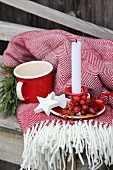 Advent arrangement of rose hips, white wooden stars and candle on fringed blanket
