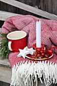 Adventliche Dekoration mit Hagebutten, weissen Holzsternen und Kerze auf Fransendecke