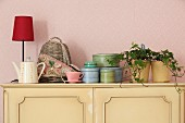 Houseplant, tins and table lamp on top of pastel yellow cabinet