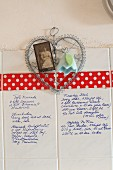 Recipe hand-written on white wall tiles decorated with vintage photo and felt flower on wire heart