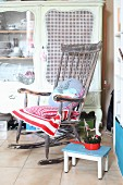 Cushions on comfortable vintage rocking chair in front of old dresser