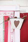 Tin bucket with love-heart motif and branch of pine cones hung from window frame with strips of fabric