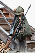 Hunting rifle, backpack, binoculars and hunting hat on newel post of rustic staircase