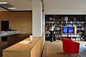 Open-plan living space with modern wooden kitchen and black metal bookcase with integrated TV