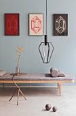 Drei gerahmte Kunstobjekte an graublauer Wand, davor Holzliege mit Polster, Pendlleuchte und Metall-Beistelltisch