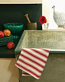 Red-and-white-striped tea towel draped over the edge of a stone sink