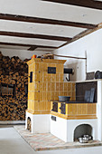 Old yellow tiled stove and wood-fired cooker next to stacked firewood
