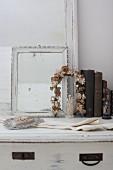 Vintage arrangement of floral wreath, mirror and books